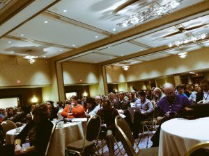 Audience listening to a speaker in a large ballroom.