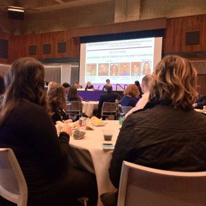 "Audience facing a slide reading ""Faculty Panel: Examining the Evidence of Student Learning."""