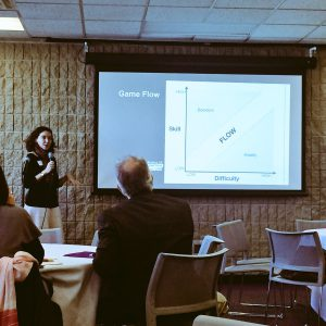 Woman speaking in front of a slide showing a graph on game flow.